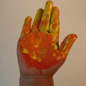 Red and yellow paint on a child's hand
