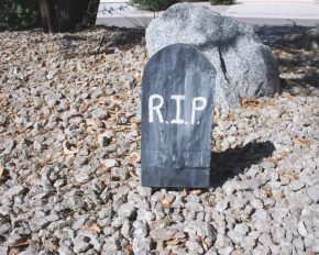 A lunch bag tombstone on gravel