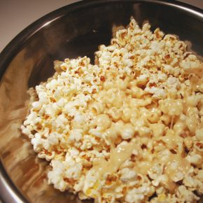A bowl of popcorn with sticky goo on it