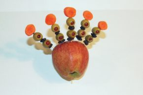 Olives, raisins and carrots on toothpicks, stuck in an apple to look like a tail