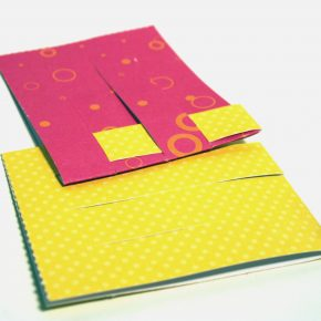 The top tab on the yellow paper has been woven into the tabs on the red paper