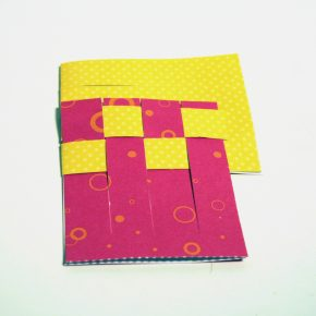 The second tab of the yellow paper has been woven into the red tabs