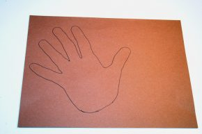 A hand traced onto brown construction paper