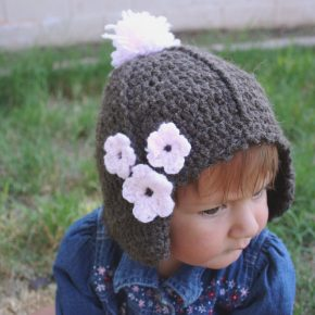 An adorable baby in a brown hat with pink flowers