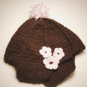 The pompom and flowers on the hat