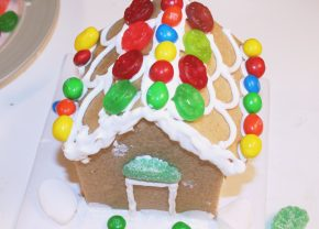 Candies are added to the gingerbread house