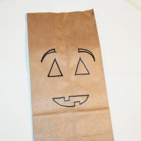 A lunch bag with a pumpkin face drawn on it