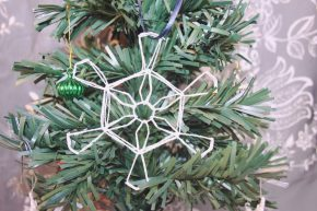 A snowflake ornament hanging on a Christmas tree