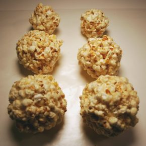 Six popcorn balls of various sizes.