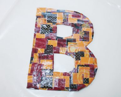 A cardborad letter covered with fall colors.