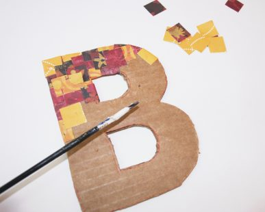 Using Modge Podge to cover a cardboard letter.