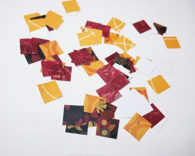 Small squares of fall colored paper