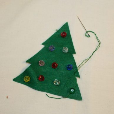 Beads being stitches onto a felt Christmas tree