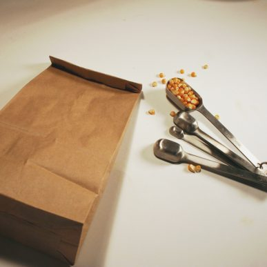 A brown bag and a measuring spoon set with popcorn kernels