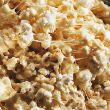 A close up of popcorn coated by a sticky substance