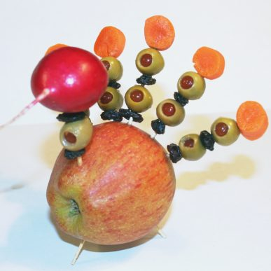 A tukey made from and apple, a radish, raisins, olives, and carrot slices