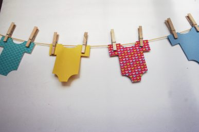 Paper onesies hanging in a row