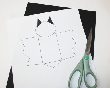 Using a pattern to cut bats out of black cardstock