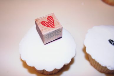 Using a stamp to decorate a cucpcake.