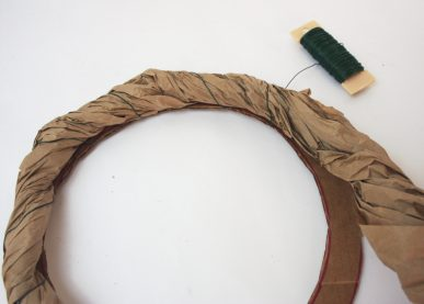 Wrapping paper around a ring of cardboard to make a wreath form
