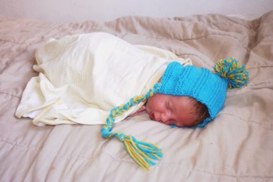 A baby sleeping while wearing a blue and yellow hat