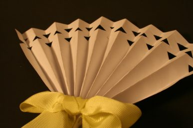 A white paper fan with a yellow ribbon