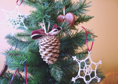 A gilded pinecone ornament hanging on a Christmas tree