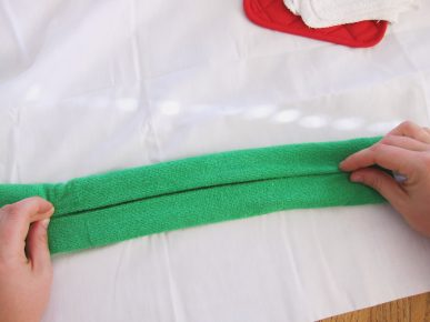 Folding a green dish towel