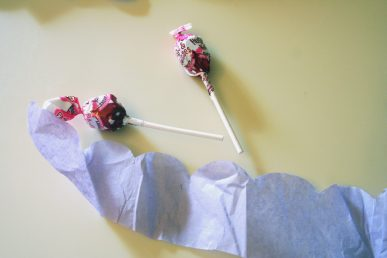 A strip of tissue paper and two lollipops