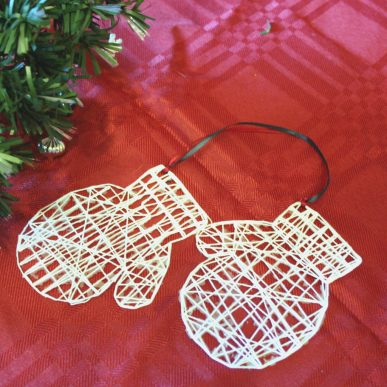 A Christmas ornament that looks like mittens made from white string