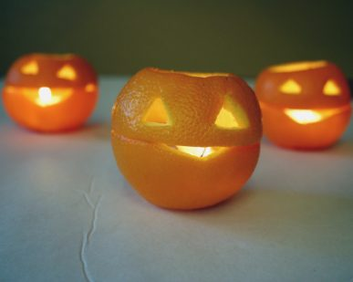Three jack o' lanterns made with oranges