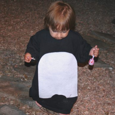 A toddler wearing a penguin costume