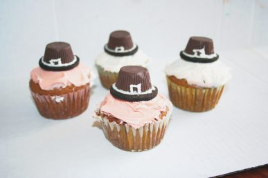 Cupcakes with pilgrim hats on top of them made from cookies and candy.