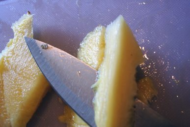 A knife coring a piece of pineapple