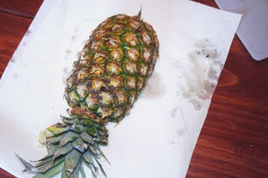 Halved and hollowed out pineapples draining on a paper towel