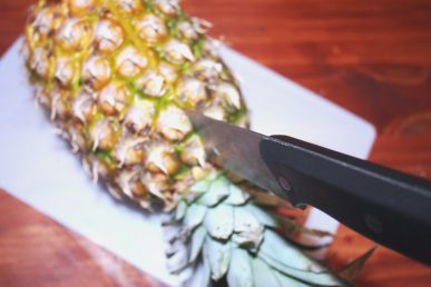 A knife slicing through the stalk of a pineapple