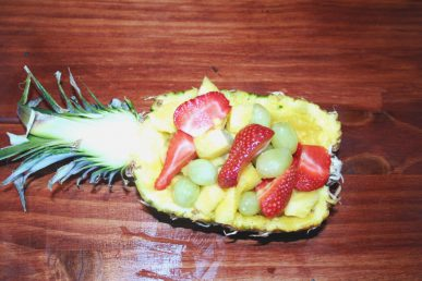 The hallowed out half filled with fresh cut fruit