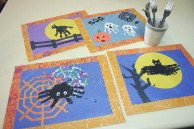 A set of four halloween placemats with handprints