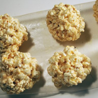 Four popcorn balls on wax paper