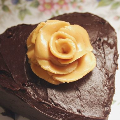A light brown rose on a chocolate heart cake