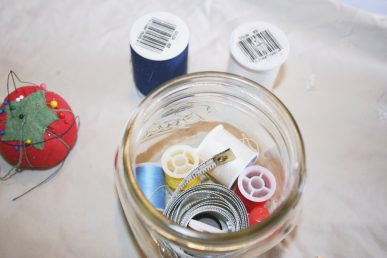Sewing supplies assembled in a jar