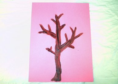 A leafless tree painted on pink paper