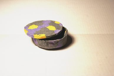 A colorful trinket box with the lid partly open