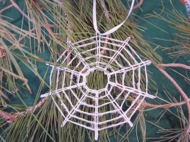 A spider web ornament made with white string