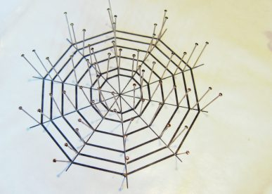A spider web ornament with pins placed in it.