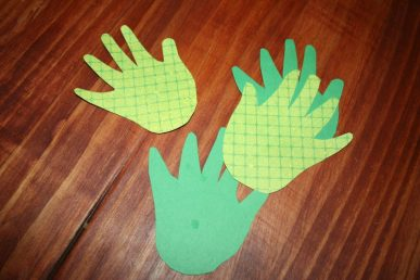 Handprints cut from green paper.