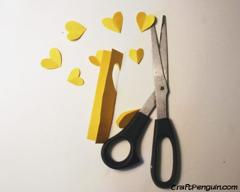 Heart cut out of yellow paper.